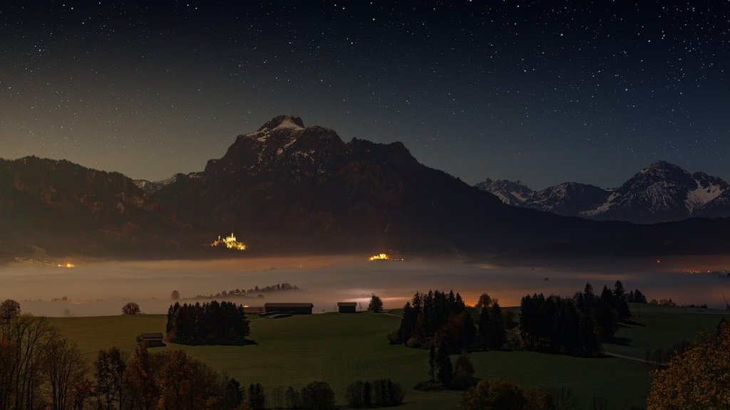 A photo showing mountains with a vast starlit sky above; and below a misty darkness save for pockets of light from human habitation.