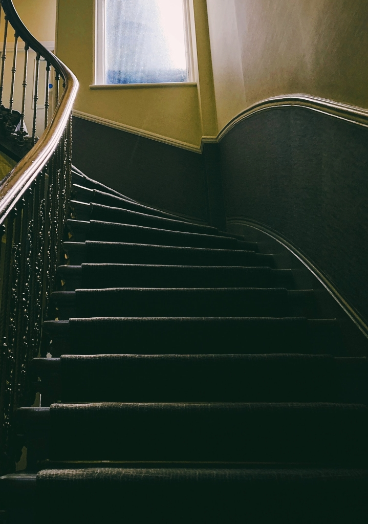 An old-fashioned staircase, with carpet, curving upwards.